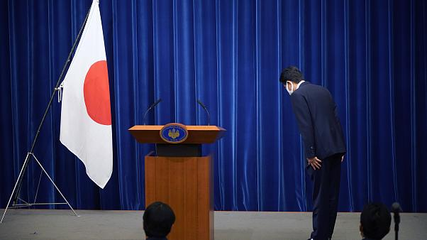 Şinzo Abe, konferans öncesinde Japon bayrağı önünde eğiliyor
