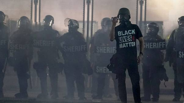 متظاهر يحمل هاتفًا وهو يقف أمام الشرطة في مدينة كينوشا الأمريكية