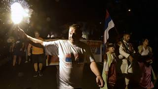 An opposition supporter lights torch during church-led protest in Podgorica, Montenegro, Thursday, Aug. 27, 2020.