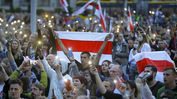 Belarusian opposition supporters with old Belarusian national flags light their smartphones as they gather at Independence Square in Minsk, Belarus, Tuesday, Aug. 25, 2020