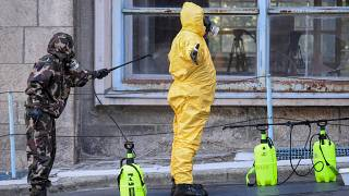 Participants of an exercise wear protective suits as they disinfect themselves in front of the Kutvolgyi hospital in Budapest.