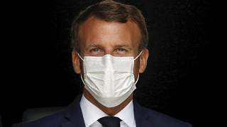 French President Emmanuel Macron, wearing a protective face mask, as he visits a site of pharmaceutical group Seqens, in Villeneuve-la-Garenne, near Paris, August 28, 2020.