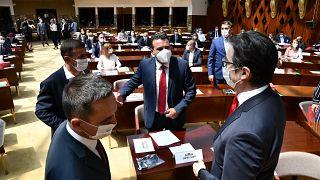 Zoran Zaev, the leader of the social democrats (SDSM), center, talks to the country's President Stevo Pendarovski, right, in parliament on Tuesday, Aug. 4, 2020