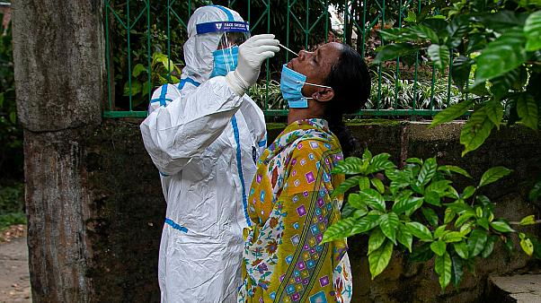 An Indian health worker takes a nasal swab sample to test for COVID-19 during a door to door test drive in Gauhati, India, Saturday, Aug. 29, 2020