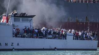 In this file photo taken on July 27, 2020, migrants arrive in Porto Empedocle, Sicily, aboard two military ships after being transferred from the island of Lampedusa
