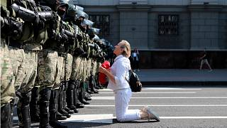 A woman kneels in front of a riot police line as they block Belarusian opposition supporters rally in the center of Minsk, Belarus, Sunday, Aug. 30, 2020