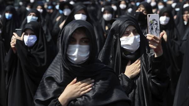 People wearing protective face masks to help prevent spread of the coronavirus mourn during an annual ceremony commemorating Ashoura.