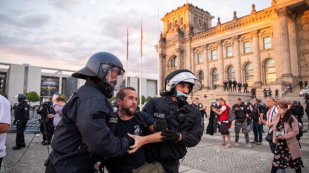 Agentes de policía alejan a una multitud de manifestantes de la plaza 'Platz der Republik' frente al edificio del Reichstag durante una manifestación, el sábado 29 de agosto.