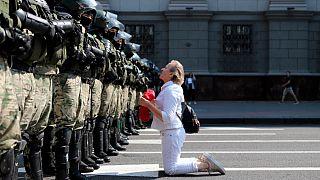 Una donna si inginocchia davanti agli agenti della polizia antisommossa, che blocca la manifestazione dei sostenitori dell'opposizione bielorussa, Minsk