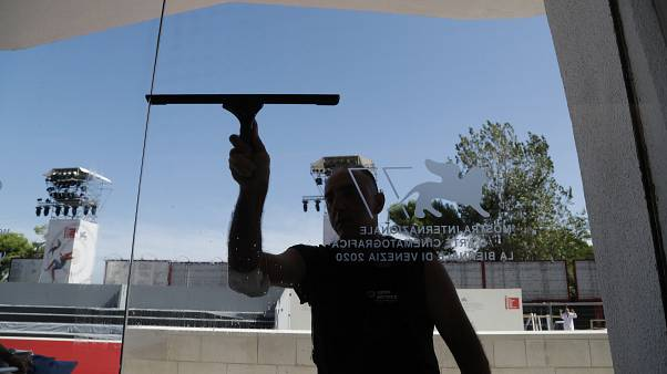 A worker cleans a glass door of the Cinema Palace at the Venice Lido, Sunday, Aug. 30, 2020.