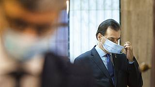 In this May 14, 2020 file photo Romanian Prime Minister Ludovic Orban handles his face mask before attending a meeting ahead of the loosening of measures taken by the state.