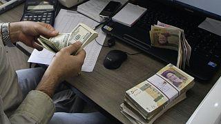 A currency exchange bureau worker counts US dollars,Tehran, Iran