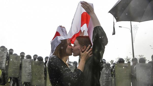 Two women kiss under an old Belarusian national flag as tens of thousands of protesters gather in Minsk