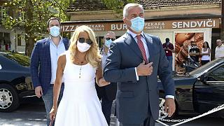 Montenegrin President Milo Djukanovic, wearing a mask, accompanied by his wife Lidija arrives at the polling station in Podgorica, Montenegro