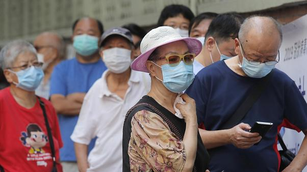 People wearing face masks queue for the coronavirus test outside a testing center in Hong Kong, Tuesday, Sept. 1, 2020.