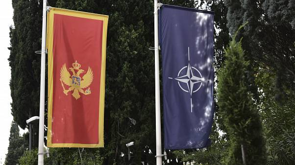 In this photo taken Monday, Nov. 11, 2019, the Montenegro, left, and NATO flags wave in front of the Montenegrin Defense Ministry in Podgorica, Montenegro.
