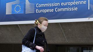 ARCHÍV: 2020. április 14. - védmaszkot viselő nő halad el az Európai Bizottság épülete előtt Brüsszelben