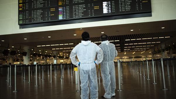Utasok védőöltözékben a brüsszeli Zaventem repülőtéren