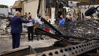 President Donald Trump talks to business owners Tuesday, Sept. 1, 2020, as he tours an area damaged during demonstrations after a police officer shot Jacob Blake in Kenosha.