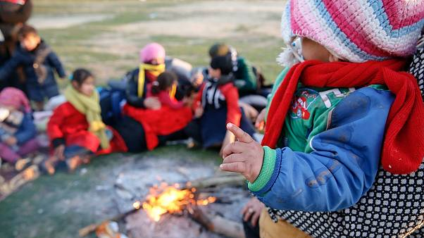 A small child is held by a fire as migrants pause on their way to Greece near Doyran, Turkey, Sunday, March. 1, 2020.