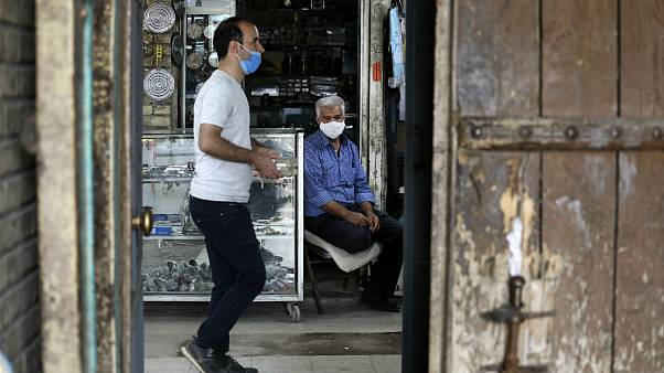 Wearing protective face masks to help prevent the spread of the coronavirus, a shopkeeper sits at his stall at the old grand bazaar of the city of Zanjan