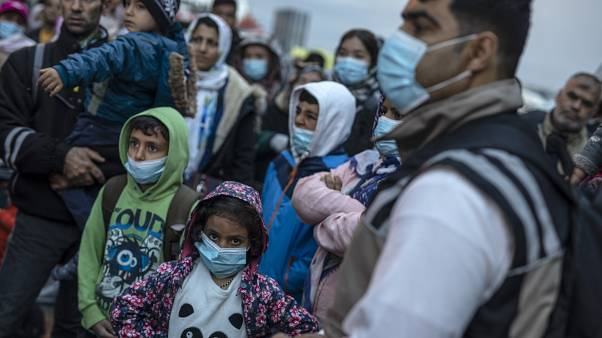 Refugees and migrants wearing masks to prevent the spread off the coronavirus, after their arrival at the port of Piraeus , near Athens, on May 4, 2020.