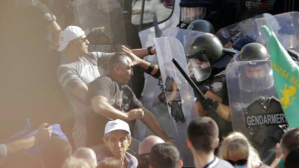 Police scuffle with protesters during rally in front of the new National Assembly building, demanding government resignation in Sofia on Wednesday, Sept. 2, 2020.