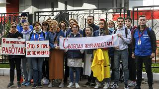 """Journalists of Belarusian TUT.BY media outlet hold banners reading """"I don't protest but work""""and """"Freedom for journalists!"""", outside a police station in Minsk, Sept. 2, 2020."""