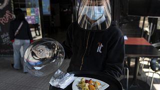 Un camarero con mascarilla y visera de protección sirve un plato en Santiago de Chile