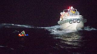 In this photo released by the 10th Regional Japan Coast Guard Headquarters, a Filipino crewmember of a Panamanian cargo ship is rescued by Japanese Coast Guard members.