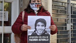 Cristina Castro, madre del joven muerto, muestra un cartel con su foto