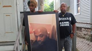 Joe Prude, brother of Daniel Prude, right, and his son Armin, stand with a picture of Daniel Prude in Rochester, New York
