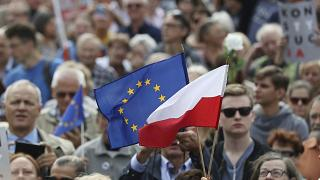 Protesters hold up a European and a Polish flag as they gather in front of Poland's Supreme Court  in Warsaw, Poland, July 4, 2018 to support the court's president.