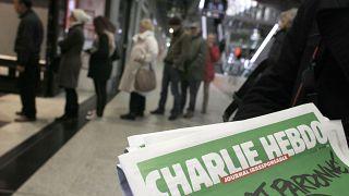 صورة من الأرشيف- يصطف الناس لشراء عدد من صحيفة شارلي إيبدو في كشك لبيع الصحف في باريس