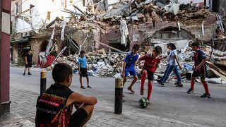 أطفال يلعبون أمام ركام أحد الأبنية المهدمة في بيروت