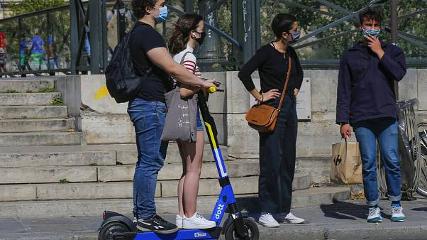 People wearing a protective face masks as precaution against the conoravirus ride a scooter in Paris