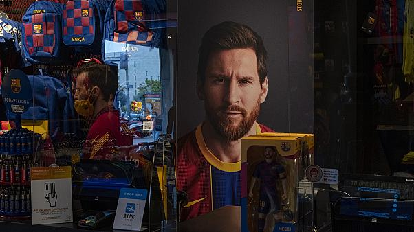 A poster with the face of Barcelona soccer player Lionel Messi is displayed at a FC Barcelona store in Barcelona, Spain.
