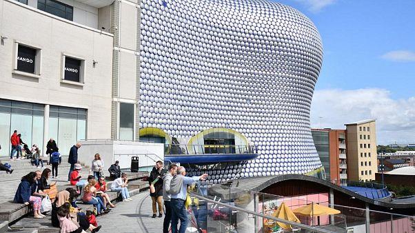Birmingham'daki Bullring alışveriş merkezinin önünde oturan insanlar (Arşiv)