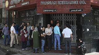 People line up in front of a currency exchange shop to buy U.S. dollars and euros, in downtown Tehran, Iran
