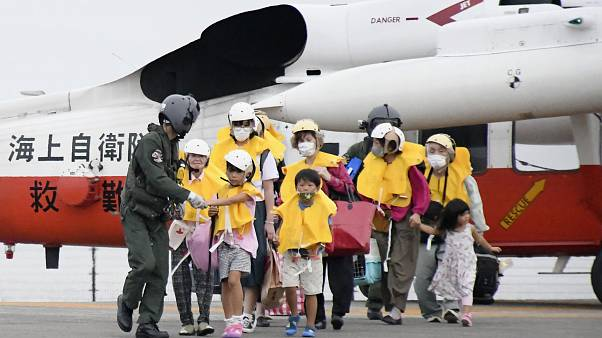 Residents arrive at a heliport in Kagoshima, southern Japan Friday, Sept. 4, 2020, to take refuge ahead of a powerful typhoon.