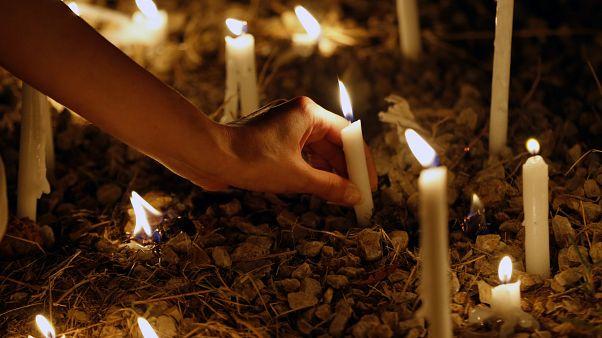 امرأة تضيء شمعة في ذكرى مرور شهر على انفجار بيروت الدموي