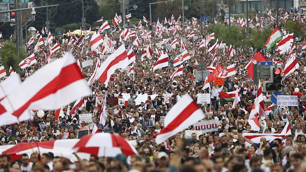 Crowds of protesters carry former Belarusian national flags during an opposition rally to protest the official presidential election results in Minsk, Belarus. Sept. 6, 2020.