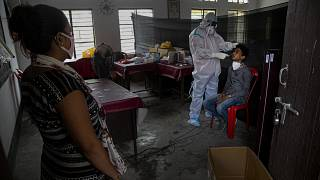 An Indian health worker takes a nasal swab sample of a man to test for COVID-19 as a woman waits for her turn in Gauhati, India, Sunday, Sept. 6, 2020.