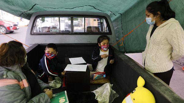 Dos niños trabajan con su profesora en el camión-escuela de Ciudad de México