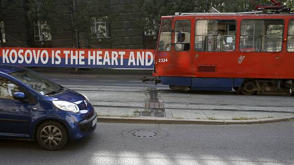 A tram car passes by a billboard reading: ''Kosovo is the heart and soul of Serbia'' placed on a street in front of the government building in Belgrade, Serbia, Sept. 2, 2020.