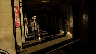 A blind man goes for a walk with his dog guide along porches of the old city during a mild winter day, in Pamplona, northern Spain