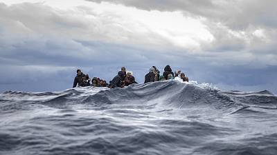 Migrants on an overcrowded wooden boat react as aid workers of the Spanish NGO Open Arms approach them in the Mediterranean Sea.