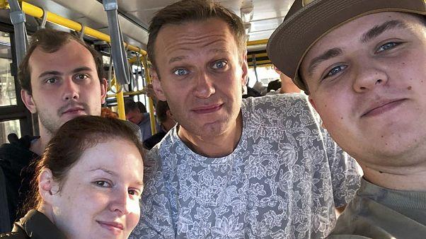 ألكسي نافالني وسط الصورة على متن حافلة باتجاه مطار خارج تومسك في روسيا. 2020/08/20