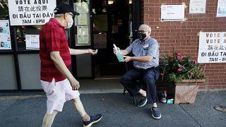 أمريكي يتطوع لتقديم مطهر الأيدي إلى الوافدين إلى مركز للاقتراع خلال الانتخابات التمهيدية في بوسطن. 2020/09/01