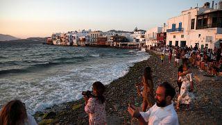 People gather as the sun sets in Little Venice on the Aegean Sea island of Mykonos, Greece, Sunday, Aug. 16, 2020.